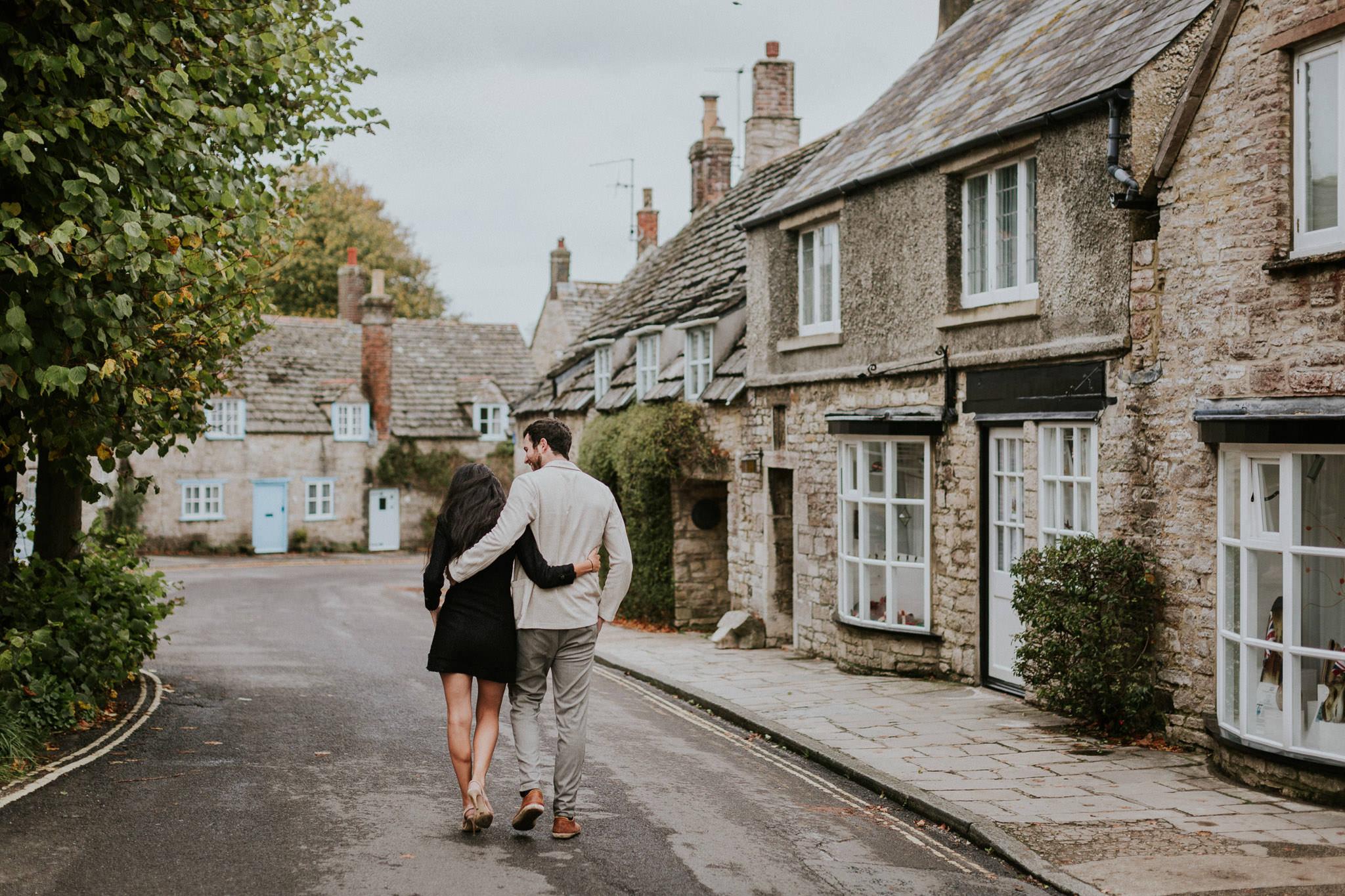 Couple walking through Corfe Castle village