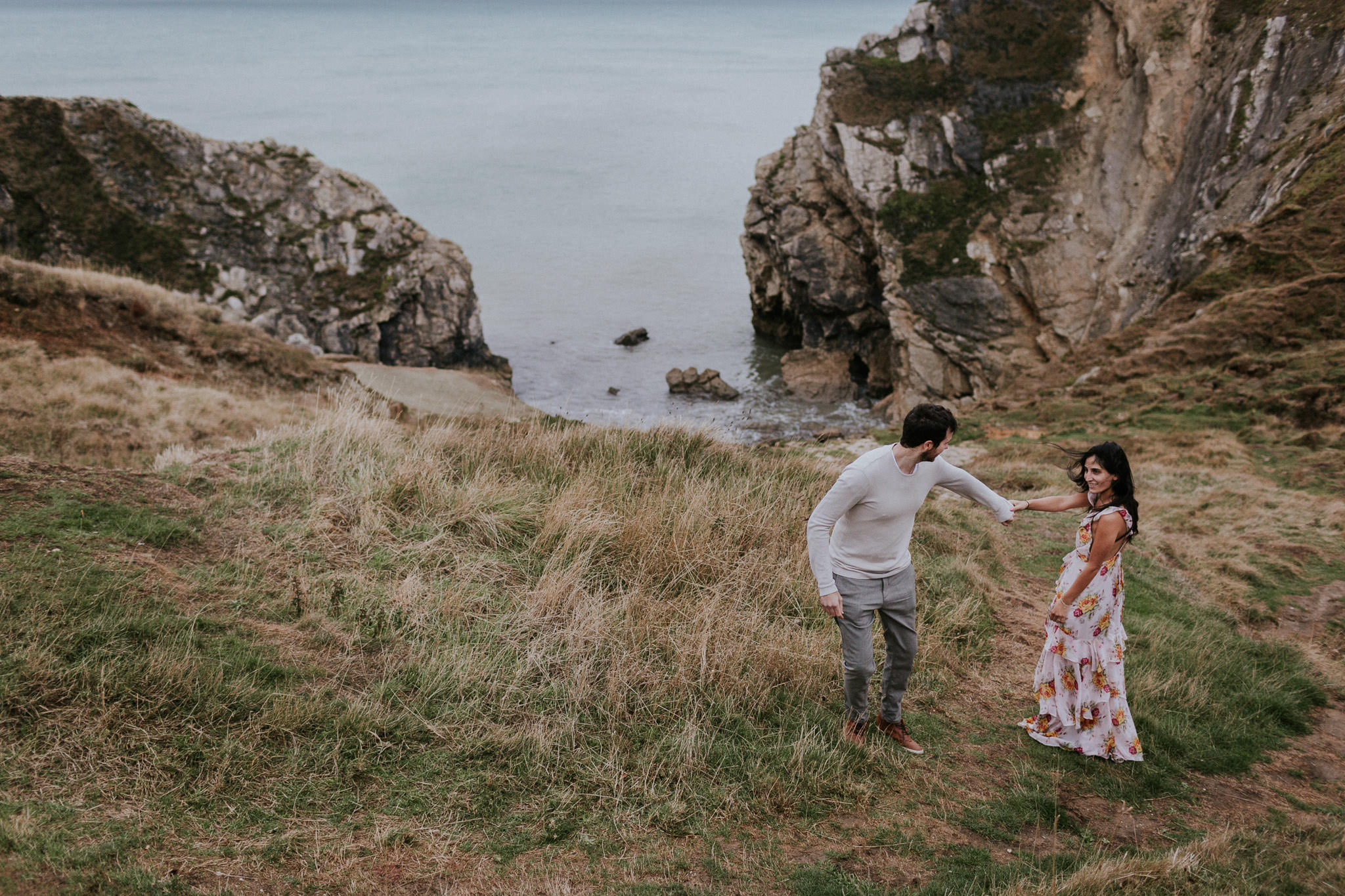 Couple walking along the coast in Lulworth Cove
