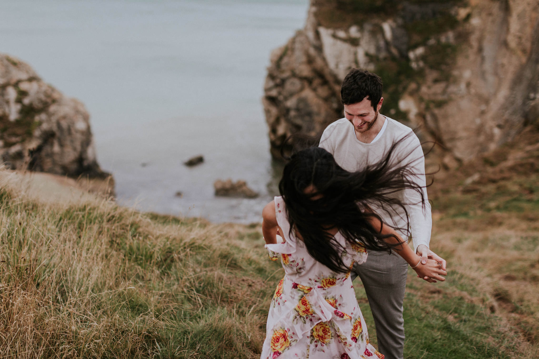 Couple smiling during their engagement photos in Lulworth Cove