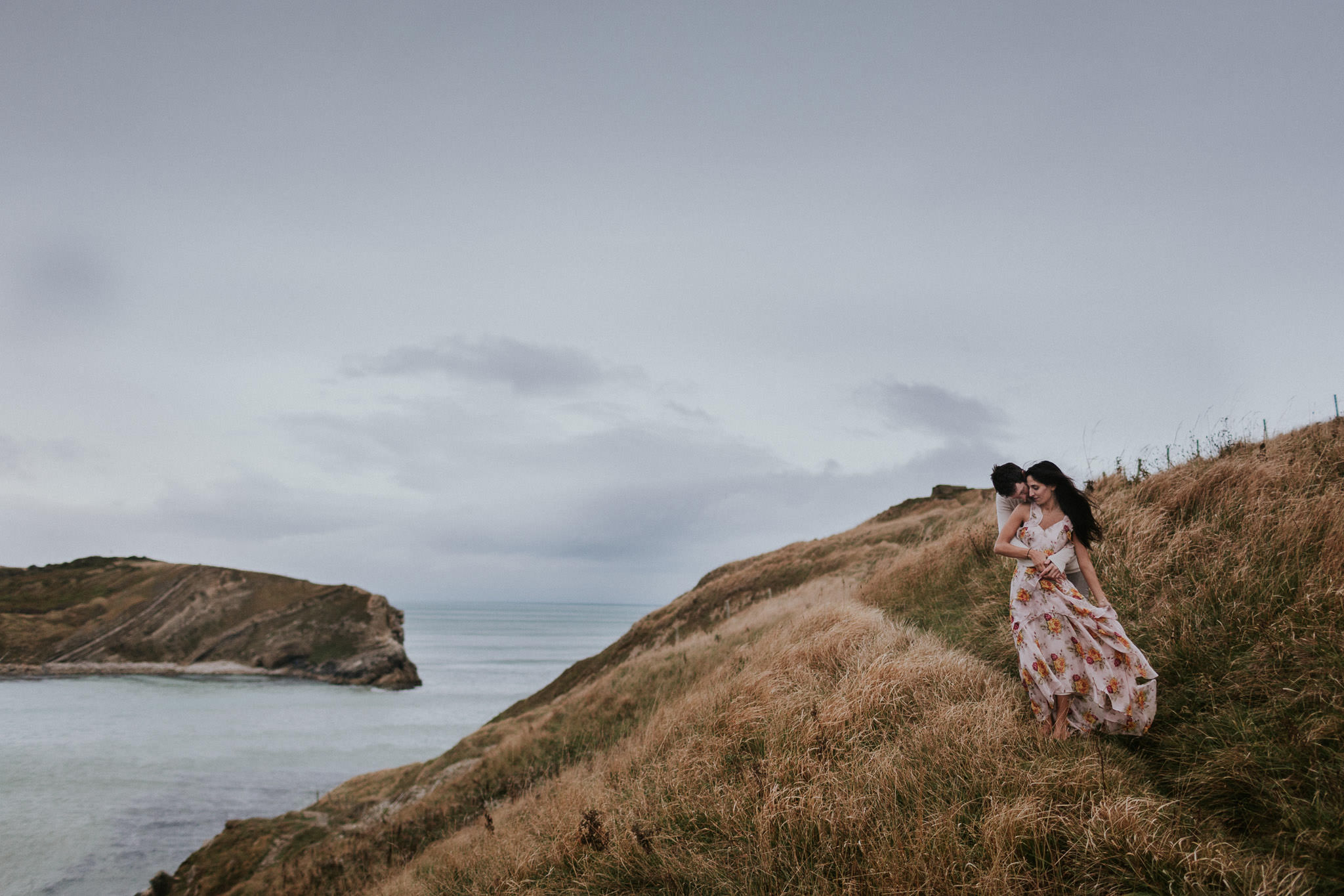 Couple embracing by the sea in Lulworth Cove