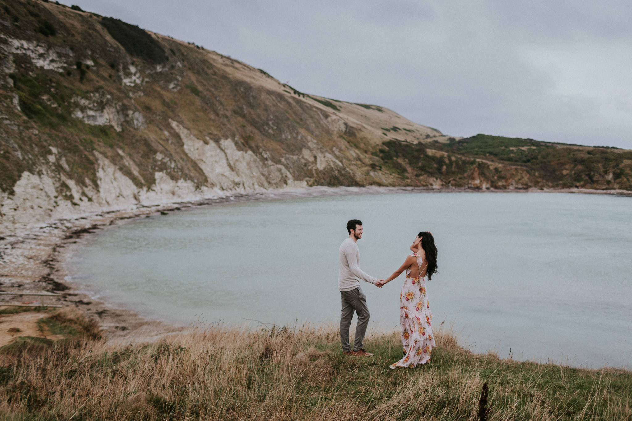 Couple walking by the sea in Lulworth Cove